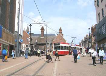 A tram calmly glides past wandering pedestrians in the town-centre pedestrian zone in Croydon.