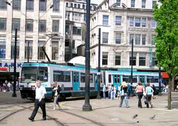 A tram calmly glides past wandering pedestrians in the city-centre pedestrian zone in Manchester.