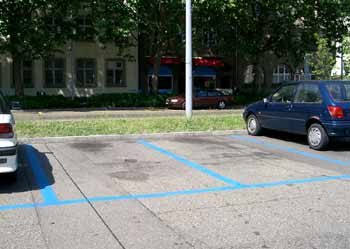 Blue coloured parking bay road markings and some parked vehicles.
