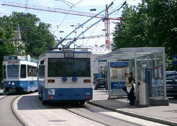 Trolleybus and tram call at road centre stop with island platforms in Zürich, Switzerland.