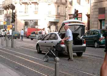 Car parked on tram tracks, driver has a babies' pushchair .