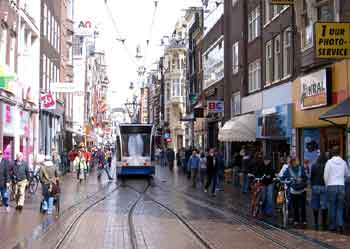 A tram calmly glides past wandering pedestrians in a narrow Amsterdam pedestrianised shopping street.