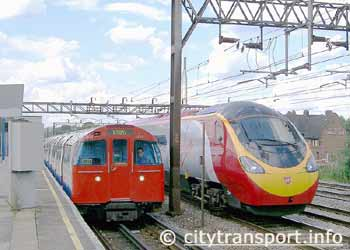 Virgin Pendolino InterCity and 1972 Mkll Bakerloo Line underground trains pass at South Kenton station London.