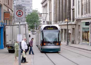 A tram calmly glides past wandering pedestrians in the city-centre pedestrian zone in Nottingham.