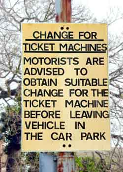 Sign says that motorists are advised to ensure they have the correct change for the ticket machine before using the car park.