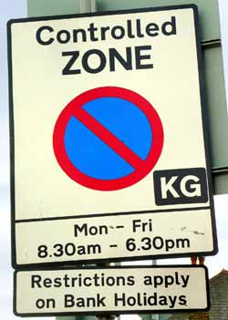 Sign has a plate below it stating that parking restrictions apply on bank holidays.