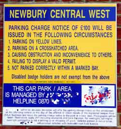Private parking contractor sign stating that unauthorised vehicles will be wheel clamped & possibly even towed away - and quoting the release fees.