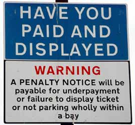 Sign warns that fines will be issued for underpayment, no payment or not parking wholly within a designated bay.