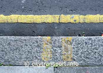 Single yellow line in gutter and somewhat faded double yellow stripes on kerbstones.