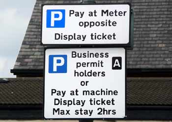 Sign next to parking bays indicating that they are for either 'pay and display' or 'business parking permit' holders.