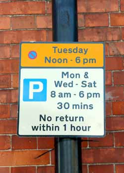 Sign shows that parking is permitted Mondays and Wednesday - Saturday, but not Tuesday.