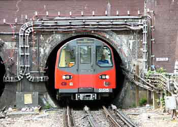 Northern Line train exits a tunnel mouth just to the north of Hendon Central station.