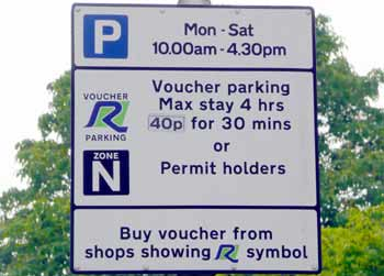 sign next to parking bay detailing that it is for residents permits and voucher owners, plus where to buy the parking vouchers.