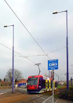 Light rail / tram / streetcar overhead wire supported from circular poles combined with street lighting too.
