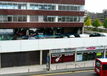 An off-street car park on the 1st floor roof above shops, with a tower block.