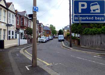 Permitted to park with one side of vehicle on kerb road sign.