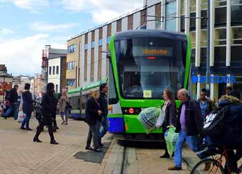 Tramlink tram and pedestrians in central Croydon.