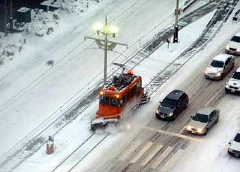 A snowbroom tram clears the track of snow.