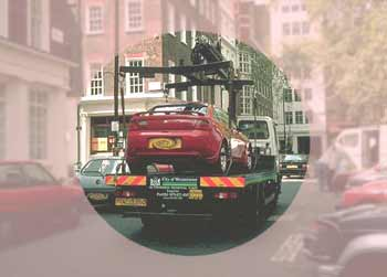 A car on an illegal-parking tow-away flatbed lorry. Seen as if looking through a rose-tinted lens with a clear central area.