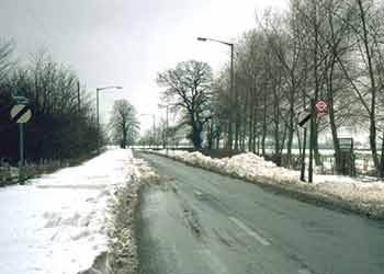 A single carriageway road with deep snow partially narrowing it so that only the road center is clear.