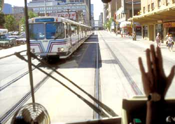 View out street-running light rail vehicles' front window, see pedestrians on footpath, empty roadway and approaching LRV travelling in opposite direction.