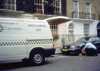Wheel clampers clamping a car.