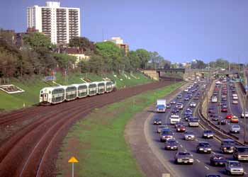 Commuter train alongside a busy urban motorway.