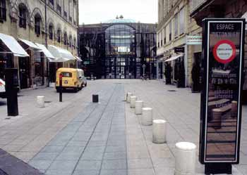 View of a pedestrian zone with bollard in raised position and post next to it showing a red signal.