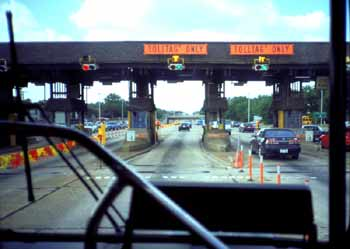 The view out the front window of a bus approaching toll booths on an American 'Freeway' (sic) in Dallas.
