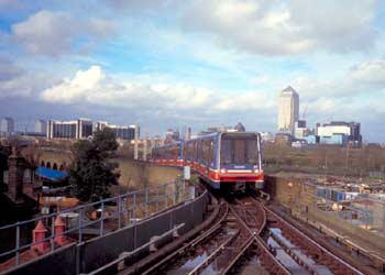 London Docklands Light Railway on a viaduct and Canary Wharf tower in the distance behind.