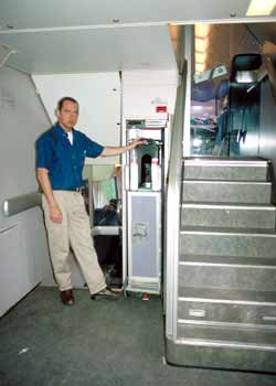 An 'at seat' refreshment trolley attendant is about to load his trolley into a double-deck train's dumb-waiter.