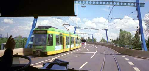 View out buses' front window, see tram approaching in other direction.