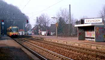 Dual-voltage light rail vehicle replacing local main-line train at Ersingen station.