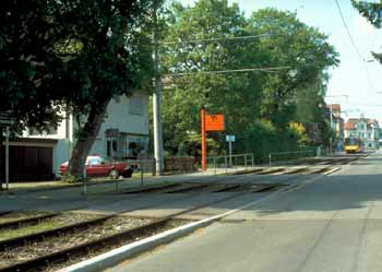 Residential driveway accesses over light rail tracks.