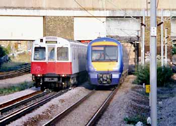 District line Underground train and C2C mainline train side by side on shared route in East London.