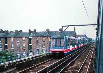 Docklands Light Railway train and C2C mainline train side by side on shared route in East London.