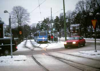 A snowy tram and roadway scene in Stockholm.