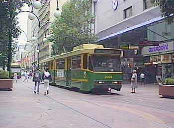 A tram calmly glides past wandering pedestrians in the city-centre pedestrian zone in Melbourne.