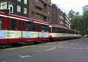 Triple unit street tram in a suburban street where it happily co-exists with road users.