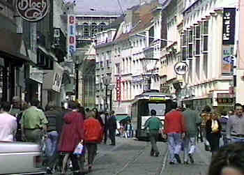 A tram calmly glides past wandering pedestrians in the city-centre pedestrian zone in Gent.