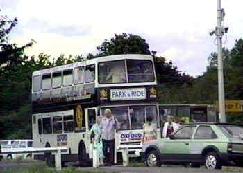 P+R car park with a double deck bus calling at a bus stop.