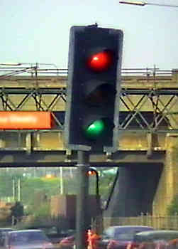 Malfunctioning traffic signals showing red and green at the same time - also leaning at unsafe angle as if about to fall over.