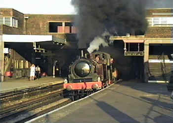 Plumes of black smoke from a steam engines as it passes through Wembley Park Station in north London.