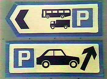 Road signs pointing to location of nearest parking facilities - for cars, lorries and coaches.